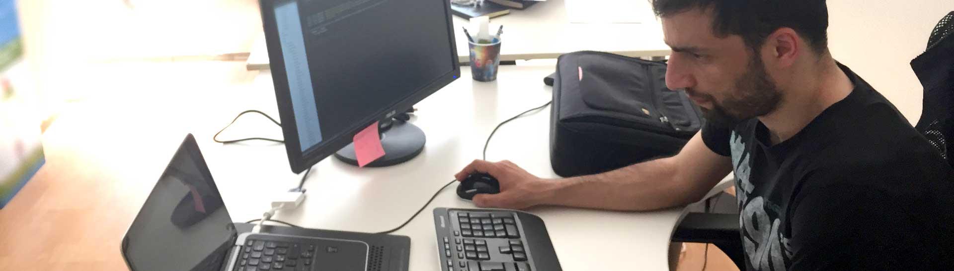 Mehmet behind computer